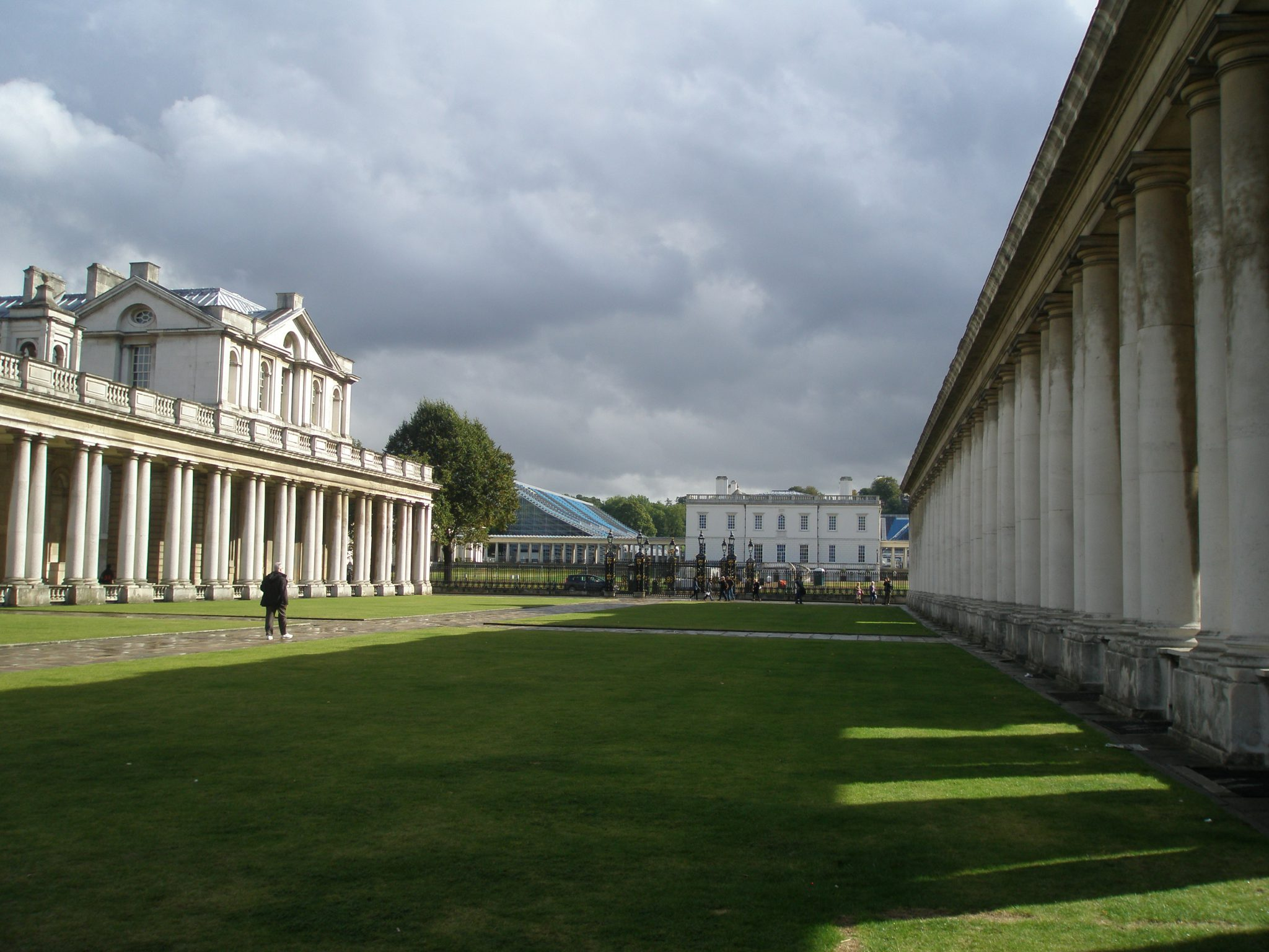 On the left: Colonnade of Queen Mary Court. On the right: Colonnade of King William Court. Center: The Queen's House, designed in 1616 by Inigo Jones for Anne of Denmark, Consort of King James I. Behind The Queen's House: temporary grandstands for the Olympics Equestrian Competitions