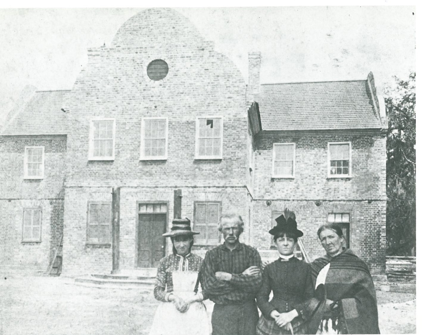 A Middleton Place tenant family, posed in front of the South Wing, the only remaining portion of the Plantation Houses. Photo taken circa 1886. Image courtesy of CHARLESTON:COME HELL OR HIGH WATER, by Whitelaw & Levkoff.