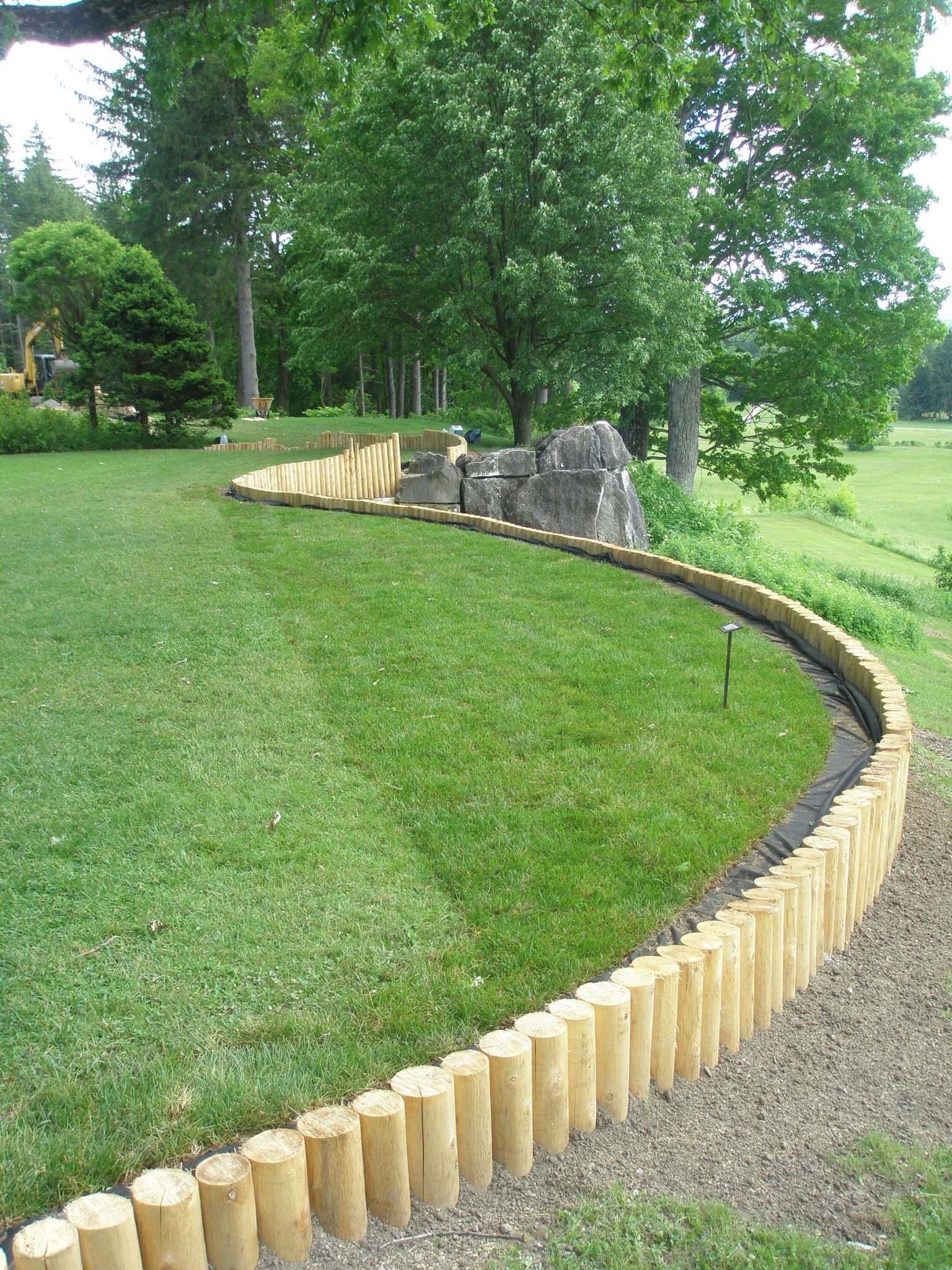 New cedar posts have been installed as the retaining wall at the Western edge of the Oak Lawn