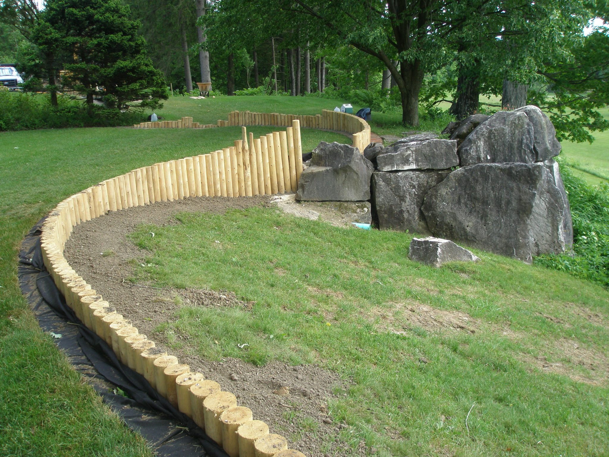 A close-up of the Oak Lawn's new cedar post retaining wall