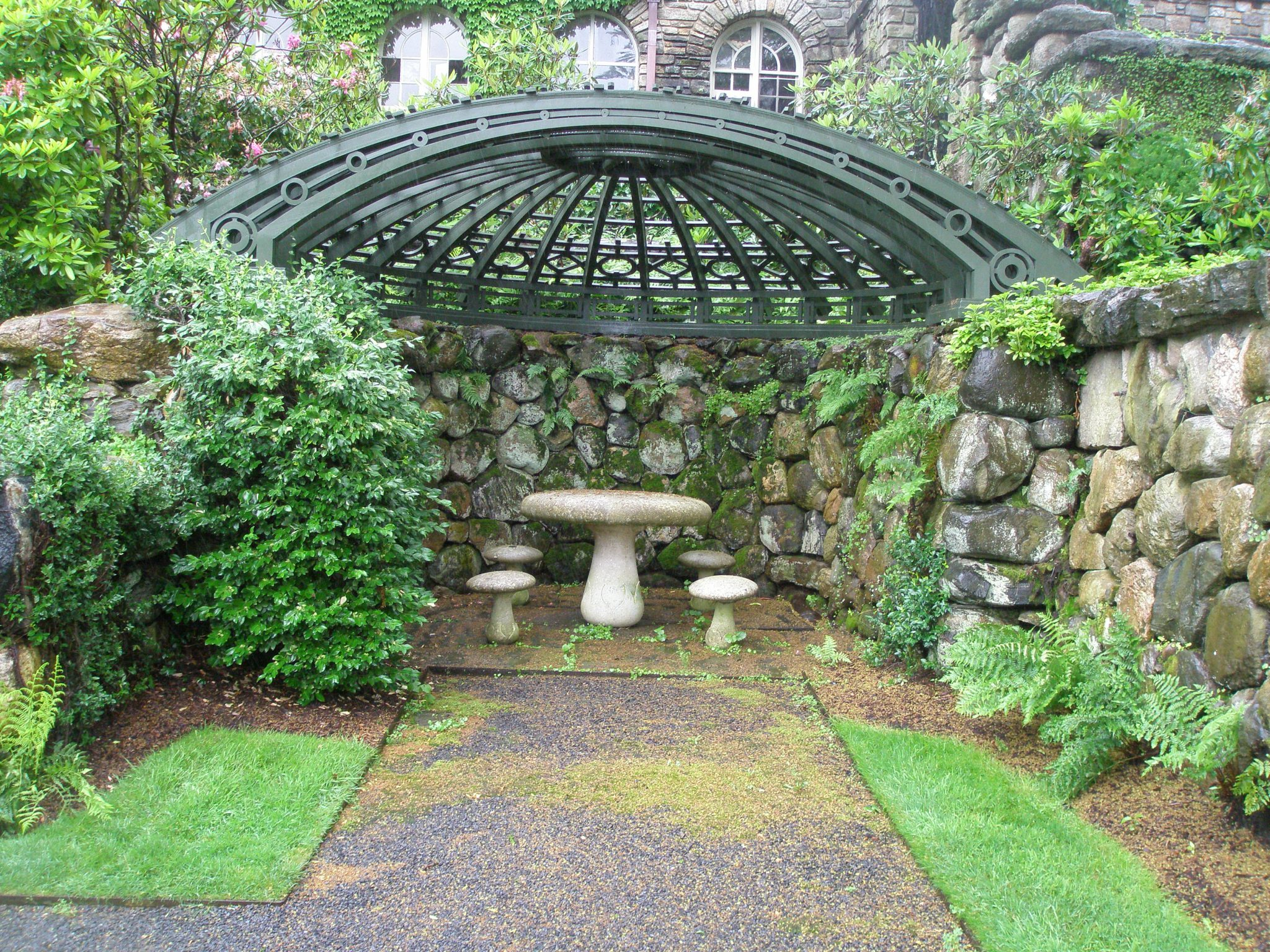 A cast-stone mushroom table and chairs are under a pergola, on the level below the Swimming Pool Terrace