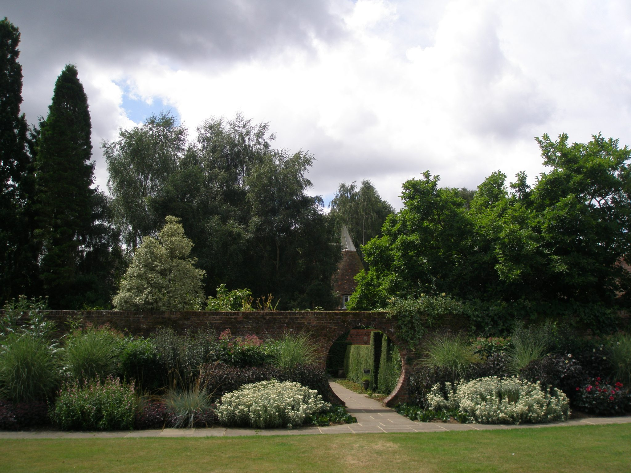 From the center of the Square Walled Garden's Lawn, we look back through the Moon Gate. This Square contains the main herbaceous border, and the annual borders.