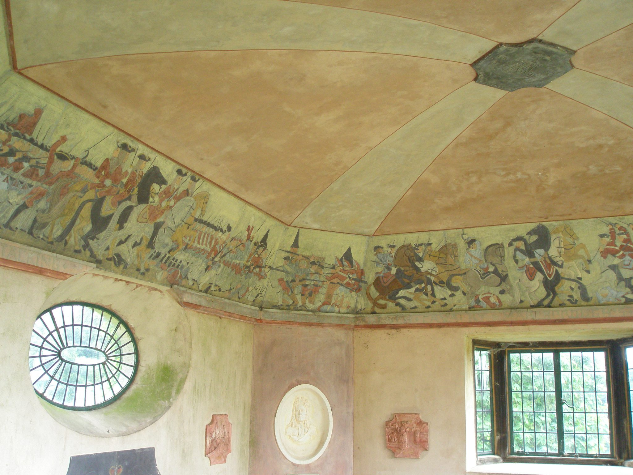 The frieze around the ceiling evokes the Marlborough wars. One panel shows the defense of the village of Blenheim; the climactic moment of the Duke's most famous victory. The Duke's grand palace in Woodstock, Oxforshire, is named after this battle. Winston Churchill was born at Blenheim Palace...but not by plan. As mentioned, his arrival came a bit ahead of schedule.