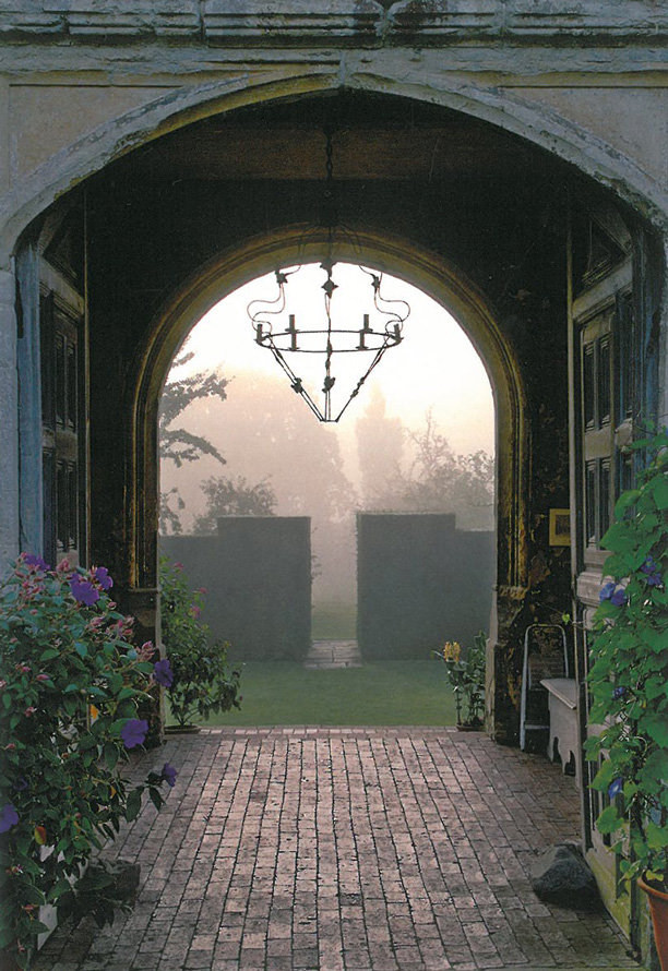 View through the Tower Arch, toward an opening in the Yew Walk. Image courtesy of The National Trust.