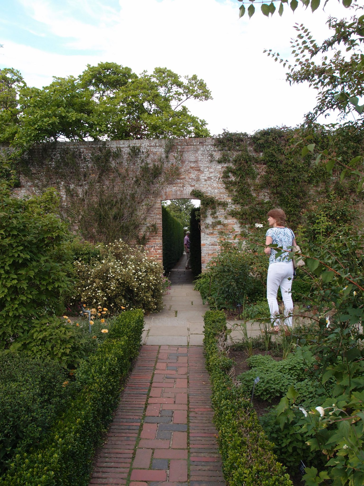 Amanda, by the Rose Garden wall, with a view down the narrow Yew Walk, which extends along the long, Eastern side of the Tower Lawn