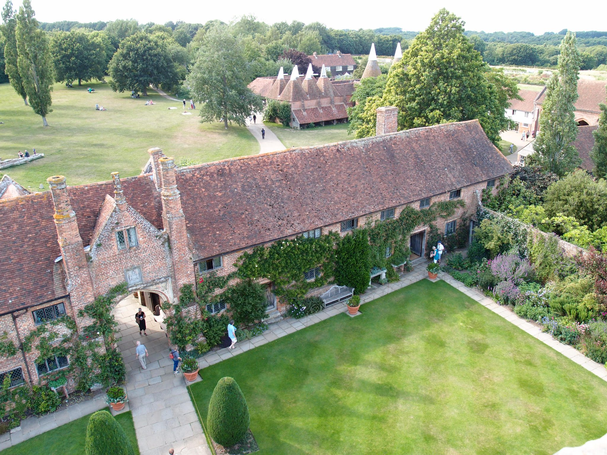 Looking Northwest. Past the front range of the Main House, which contains the Library at the northern end, is a complex of Oast Houses.