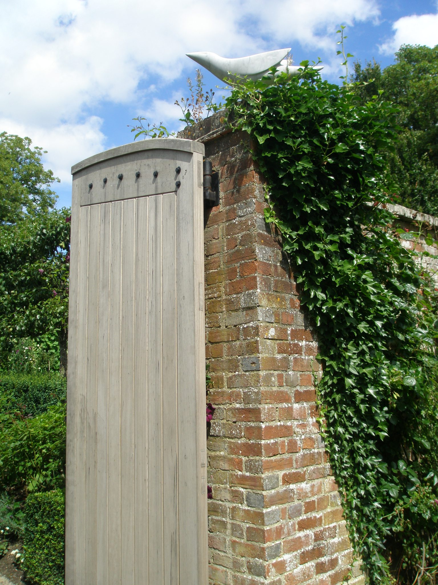 ABSTRACT DOVE, a marble by Ev Meynell, alights upon the main gate to the Walled Garden