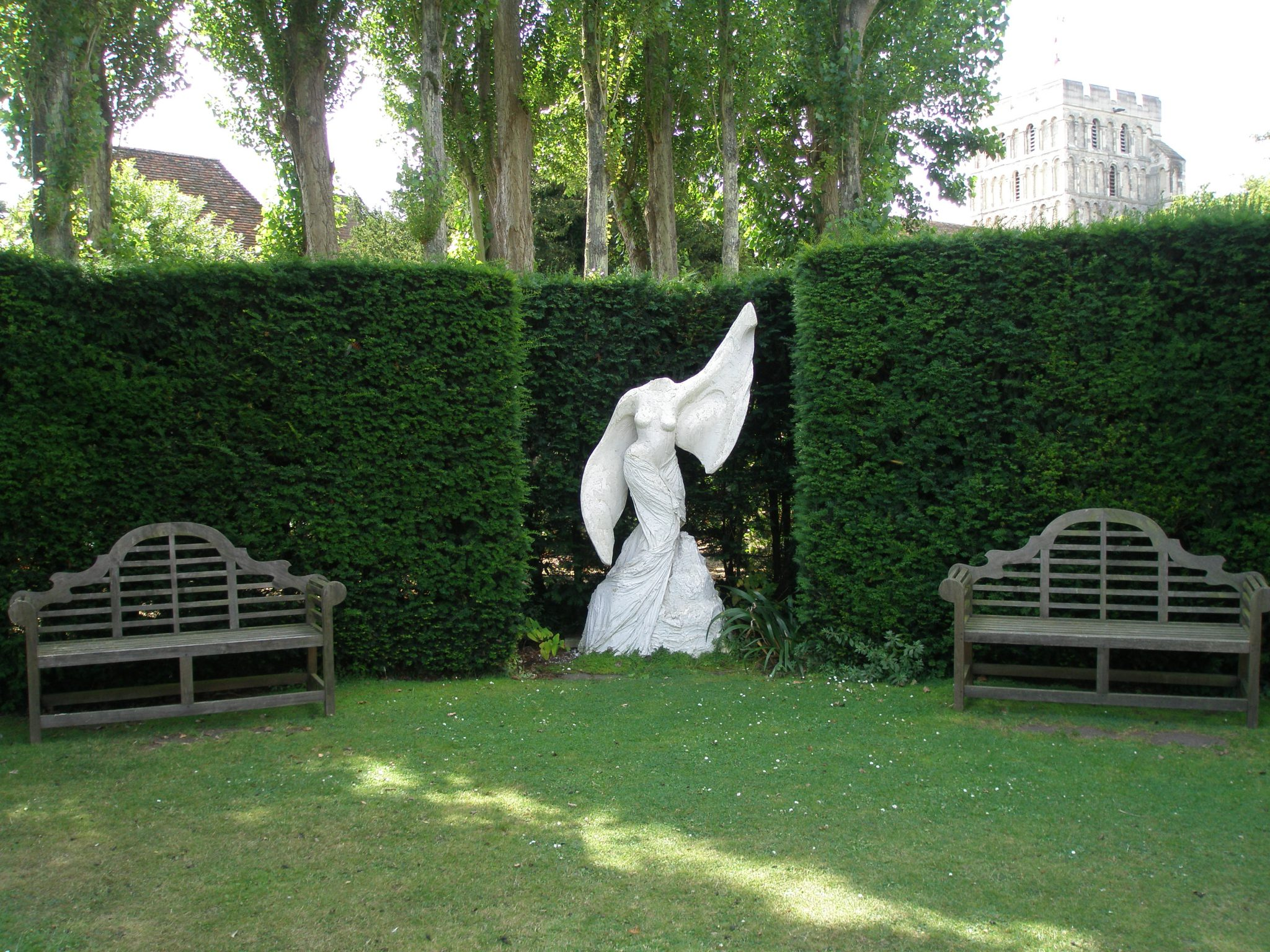 In the end-most curve of the hedge that encloses the Bowling Lawn: two more of Lutyen's Signatue Benches flank a joyous Angel Statue. In the background: a glimpse of one of the ancient buildings in the town of Sandwich, which was one of the original Cinque Ports; established in the 12th century to defend England's south coast from invasion.