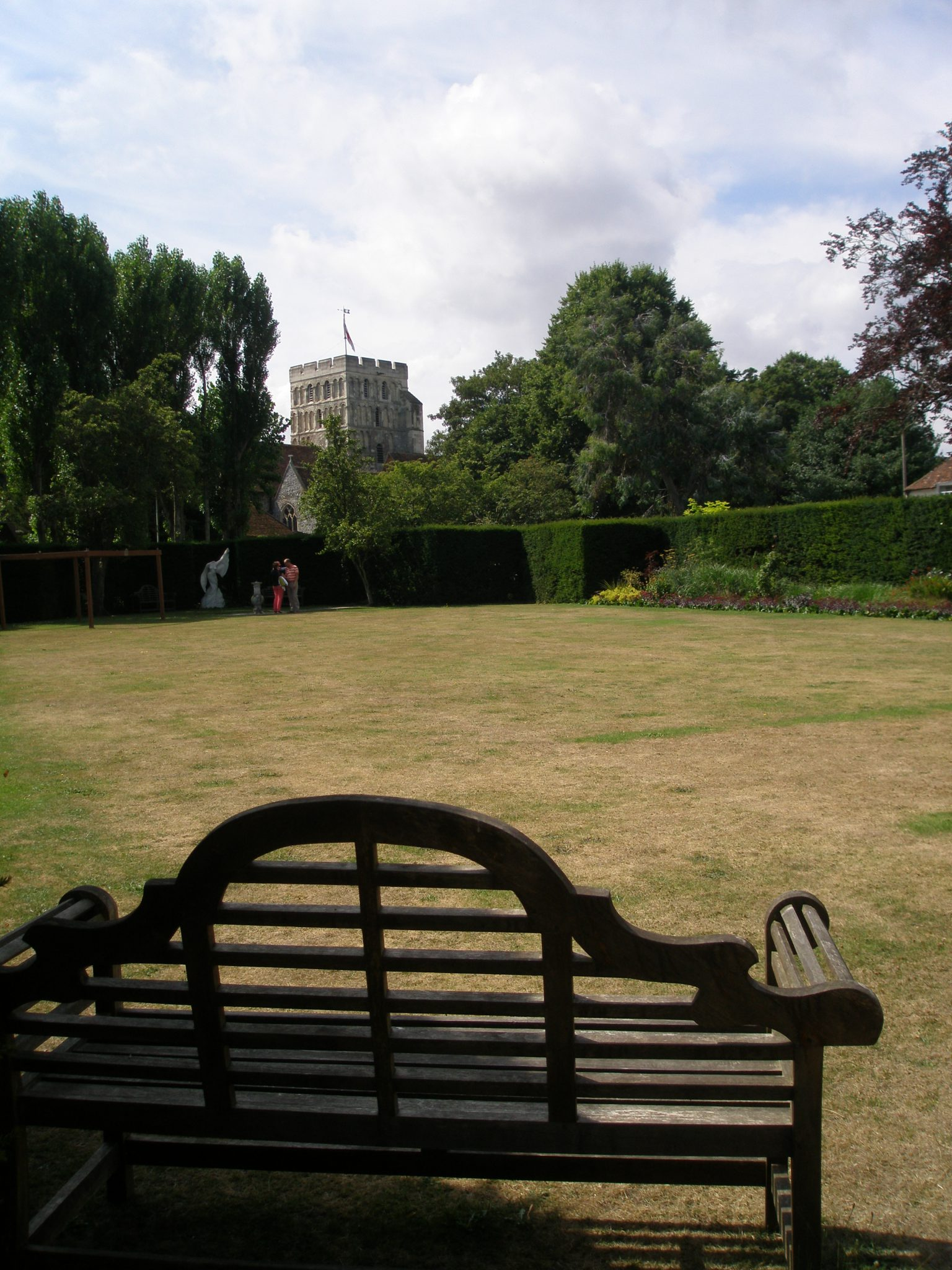 A long view across the sunburnt green of the Bowling Lawn