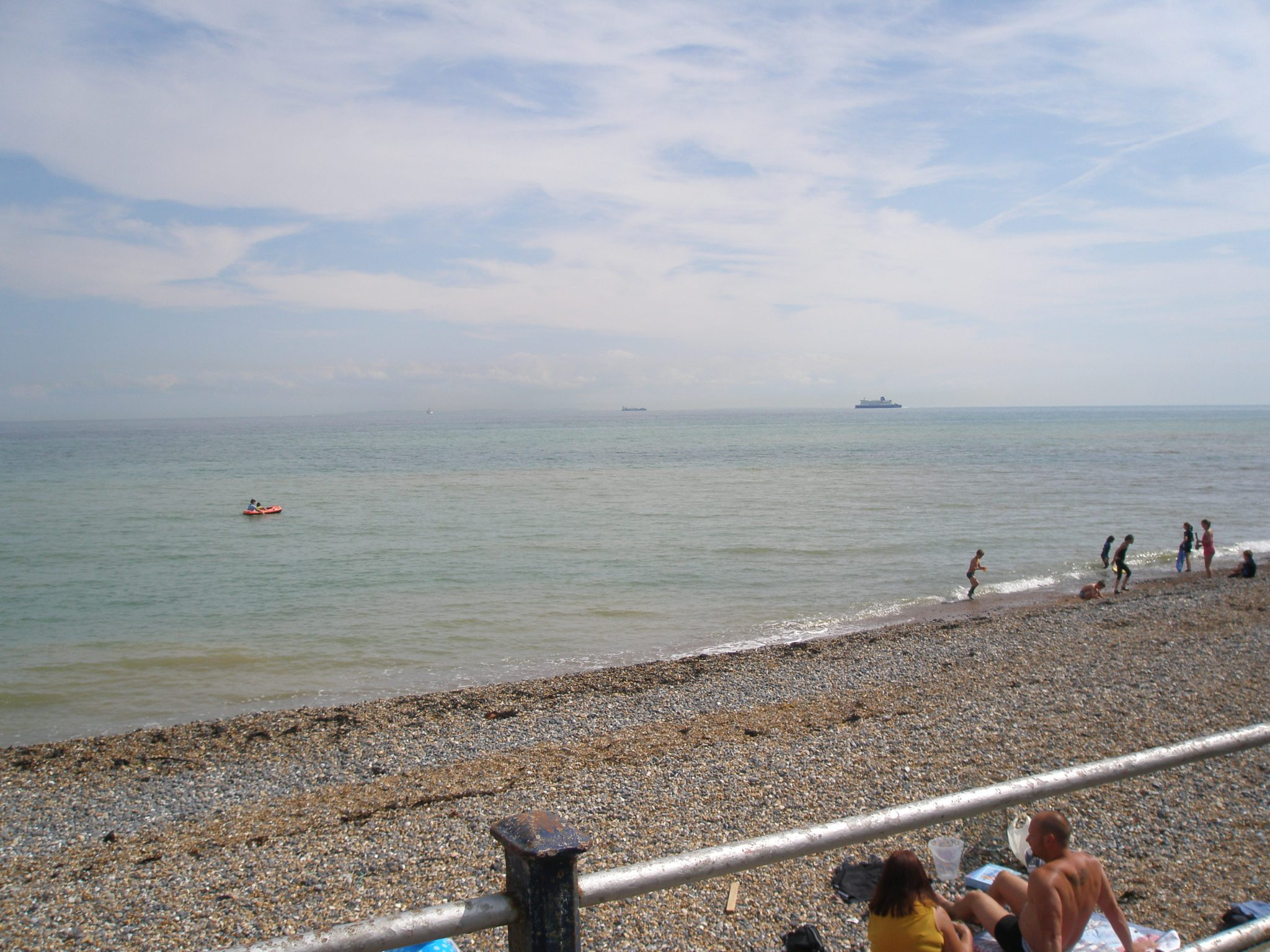 Beach-goers lounge on the rough, single beach, while an endless armada of ships passes, on the English Channel. On the far horizon, France can be seen, as a thin smudge of darker blue.