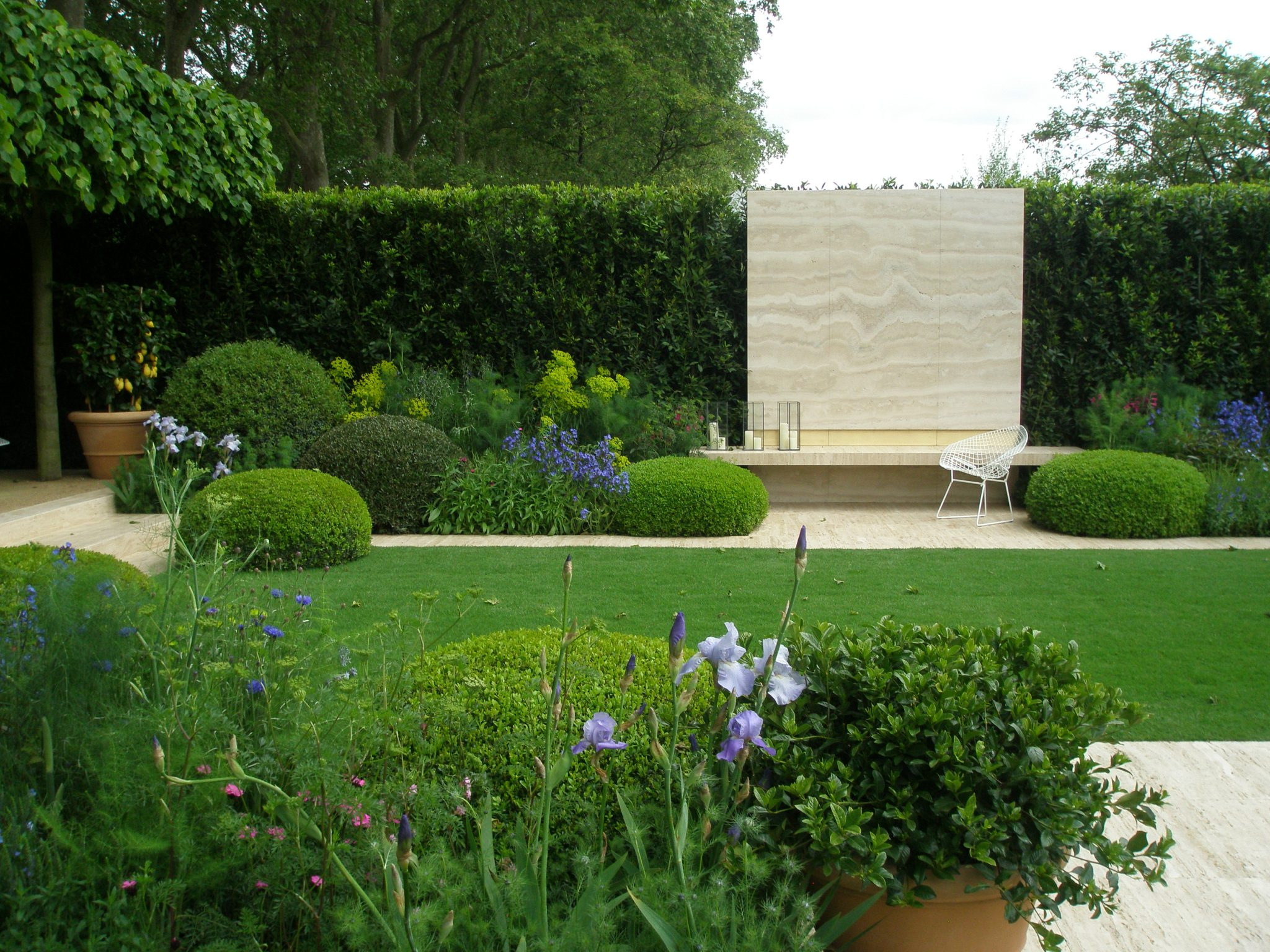 The Daily Telegraph Garden, at the 2014 Chelsea Flower Show. This is just a portion of the elegant space designed by Tommaso del Buono and Paul Gazerwitz. Tommaso grew up in Florence, and Paul in New York, and together they have an international practice, based in Shoreditch, East London. Here, a giant panel of Nocino Travertine Limestone punctuates a tall, green hedge. Low topiaries, pruned into pincushion shapes, flank a bench that floats in front of the limestone.