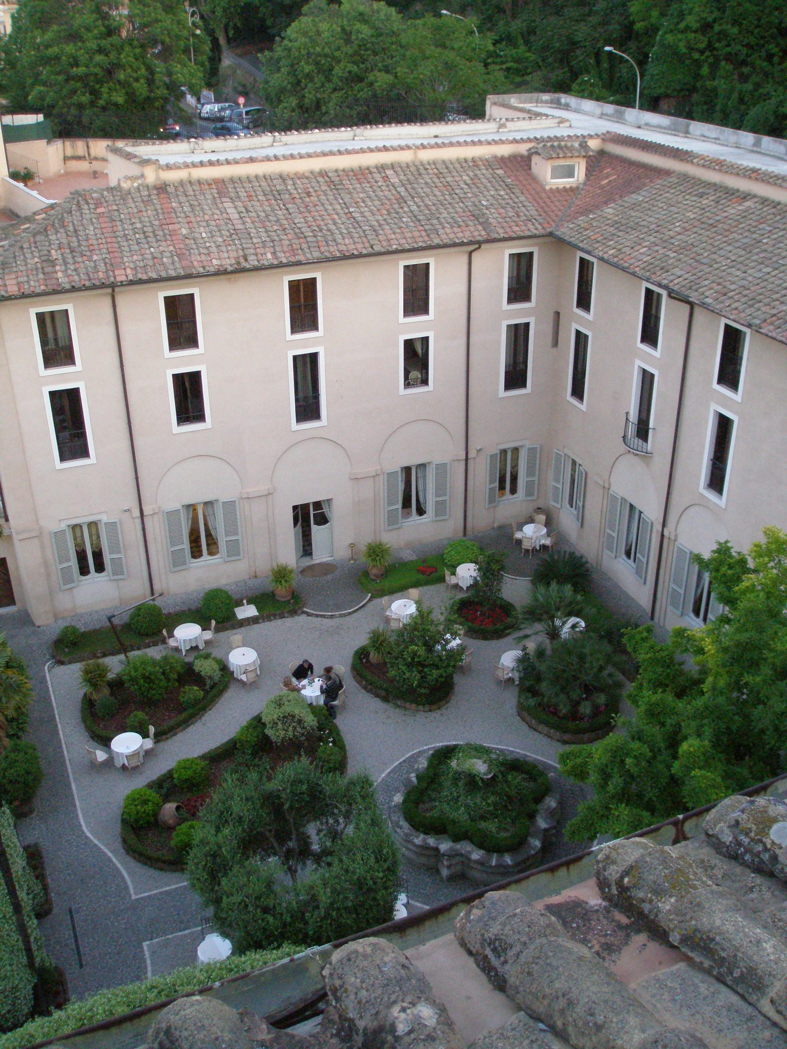 The Donna Camilla Savelli Hotel. This is my twilight view of the courtyard, as seen from the Hotel's roof terrace, which is built atop Borromini's Church of Santa Maria dei Sette Dolori. The window to my too is on the top floor of the former Convent, & just to the right of the corner where two wings of the building meet. Photo taken on Friday, May 9, 2014.