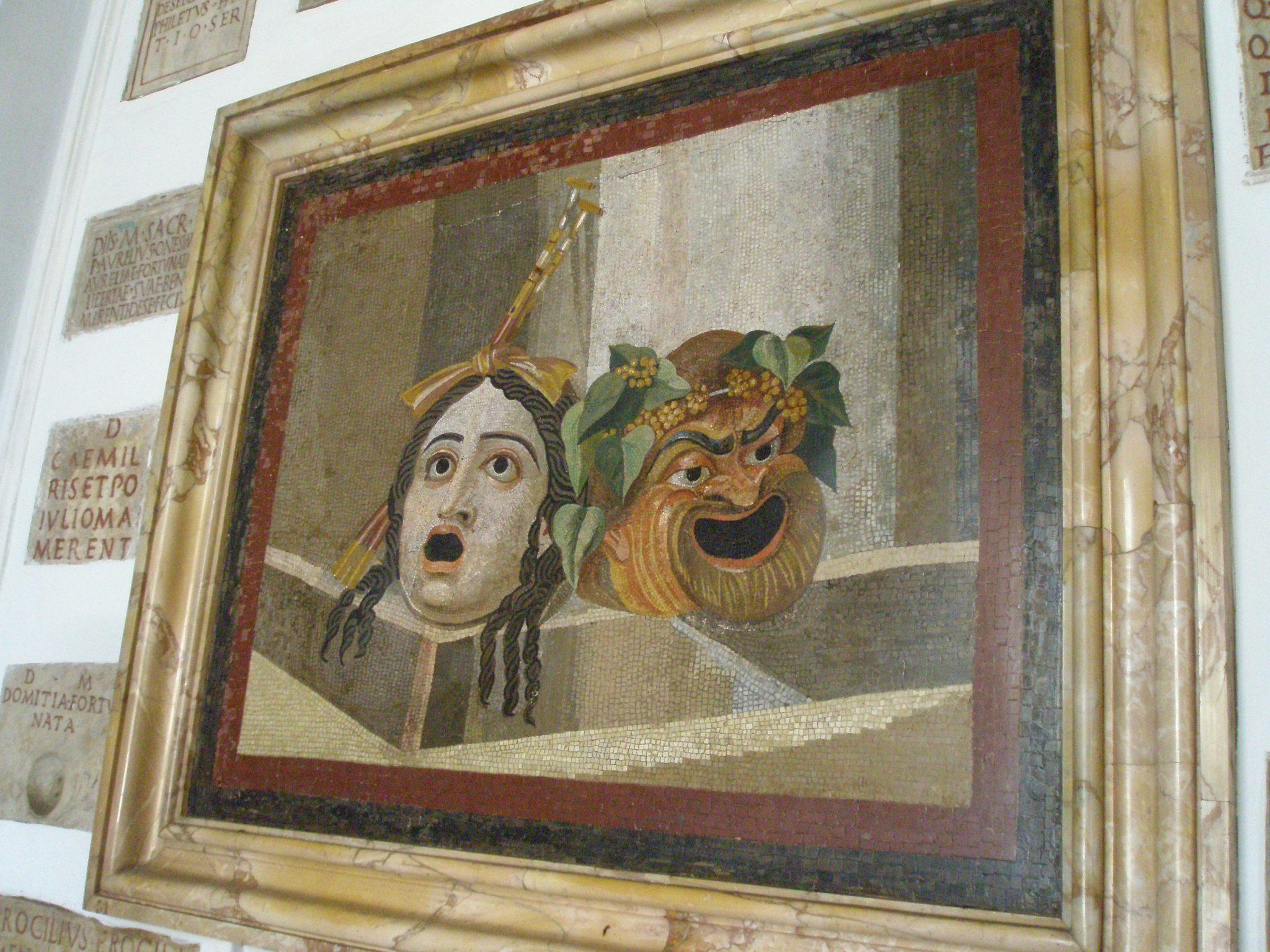 Mosaic of theatrical masks, displayed in the Palazzo Nuovo. This mosaic was recovered from the site of the Trajan Baths, which were constructed from 249--251AD.