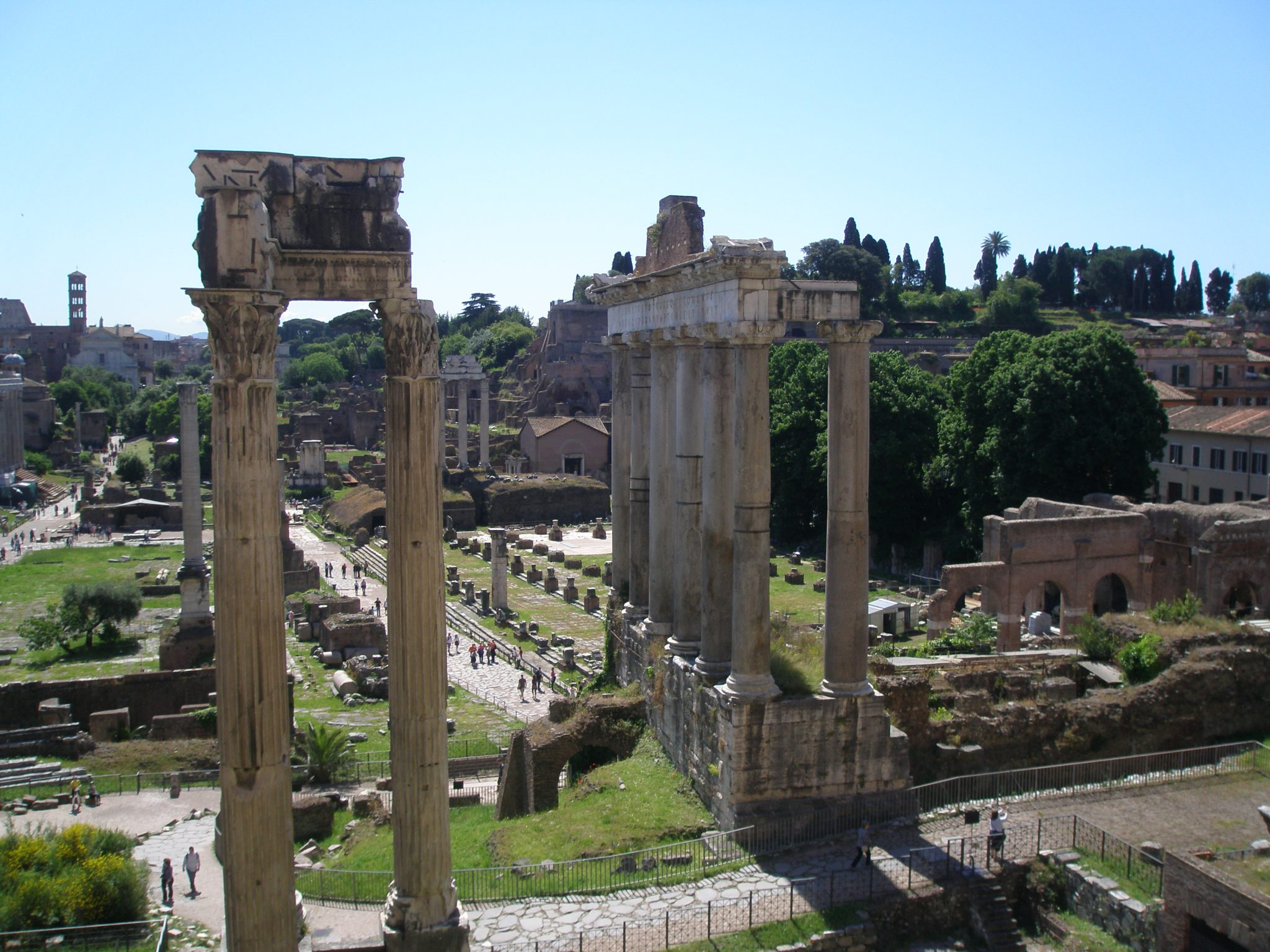 Seen from the Tabularium: in the foreground, another view of the Temple of Concord, & the Temple of Saturn. The orderly progression of column footings in the central, middle-ground mark the location of the Basilica Julia. The Palatine Hill is in the background.