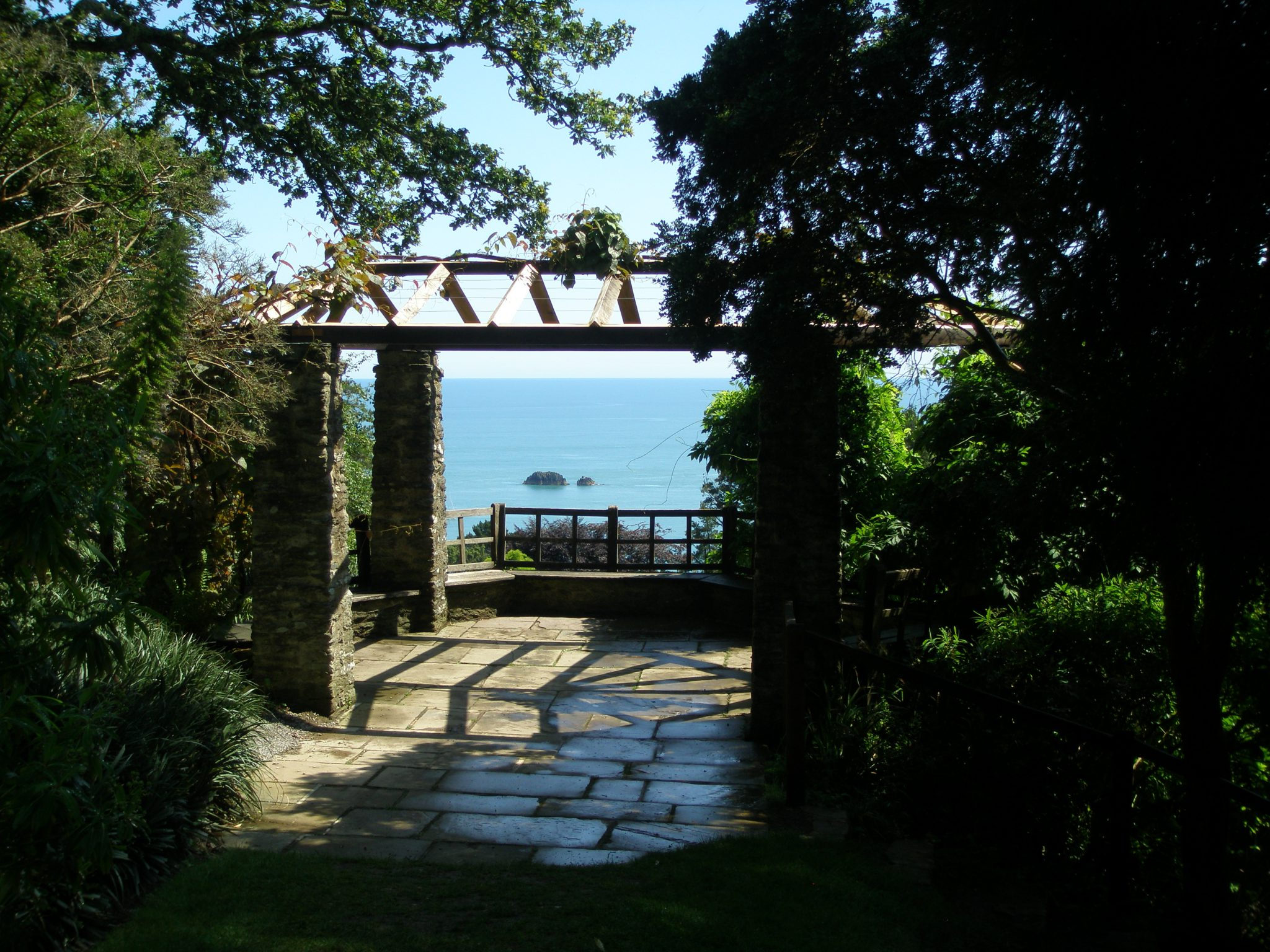 The hexagonal Gazebo, with stone pillars and wooden trellis supporting wisteria, has a spectacular ocean view. When first built, the Gazebo also had a clear view, back to the House.