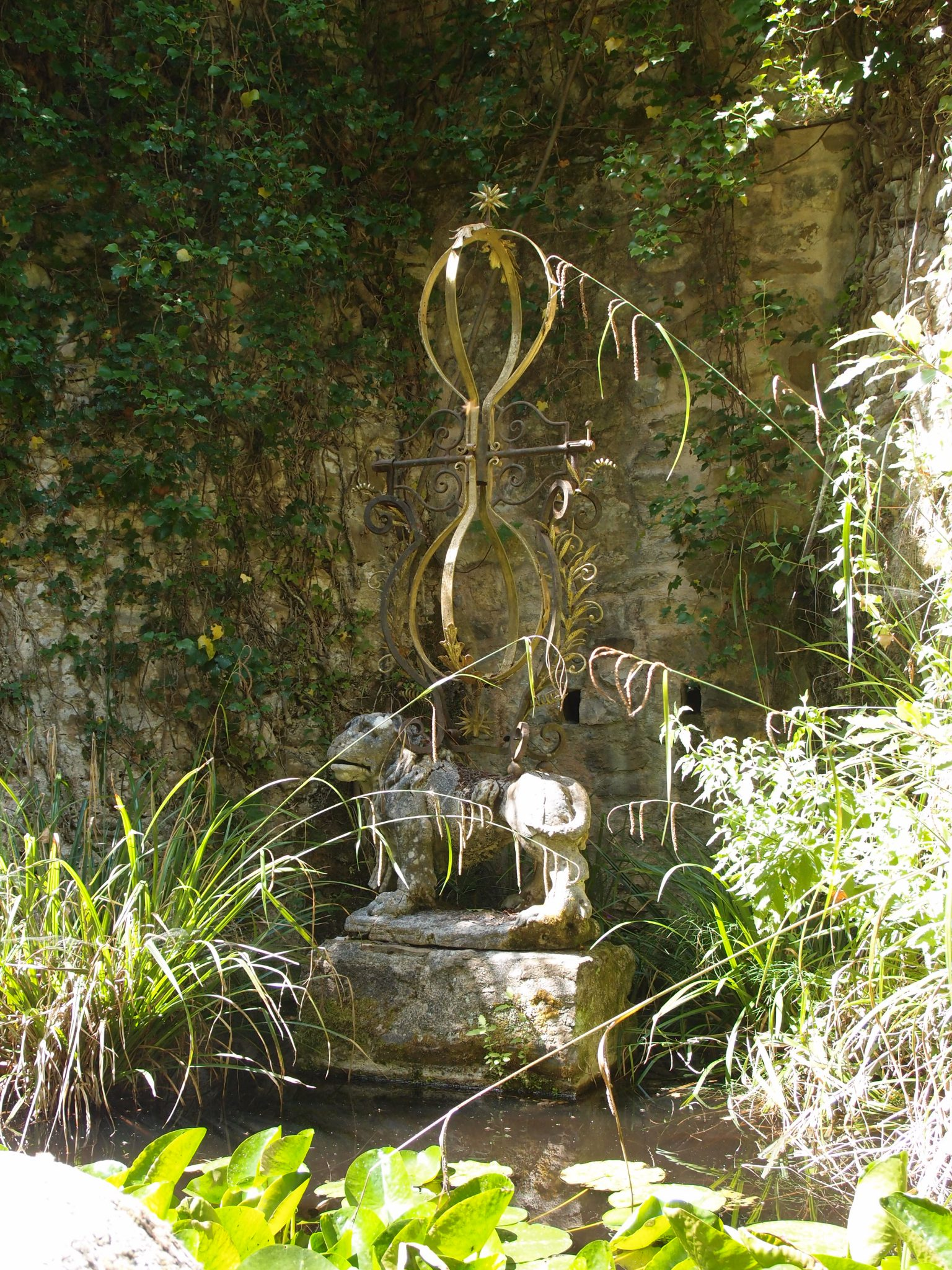 A hybrid ornament --ancient statue with new brass filigrees -- decorates the Lily Pond.